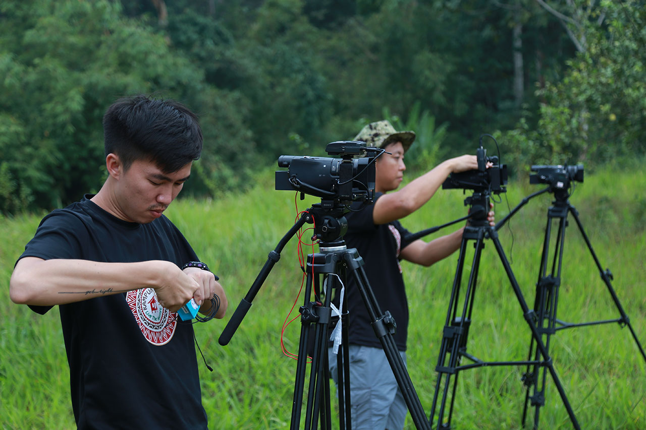 Cinematography team preparing AX100 cameras on the set of Kampung Quest reality show in the jungle.