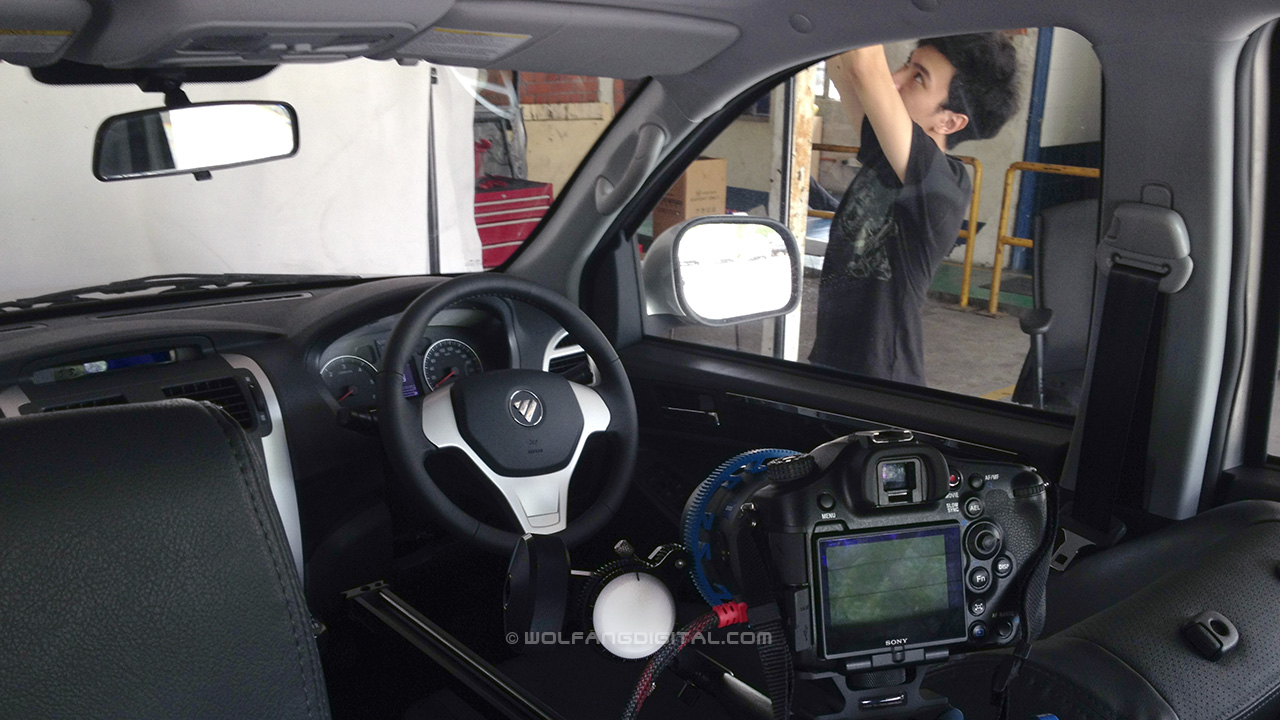 Setting up a car interior shot with Sony A99 and LED lights for corporate video.