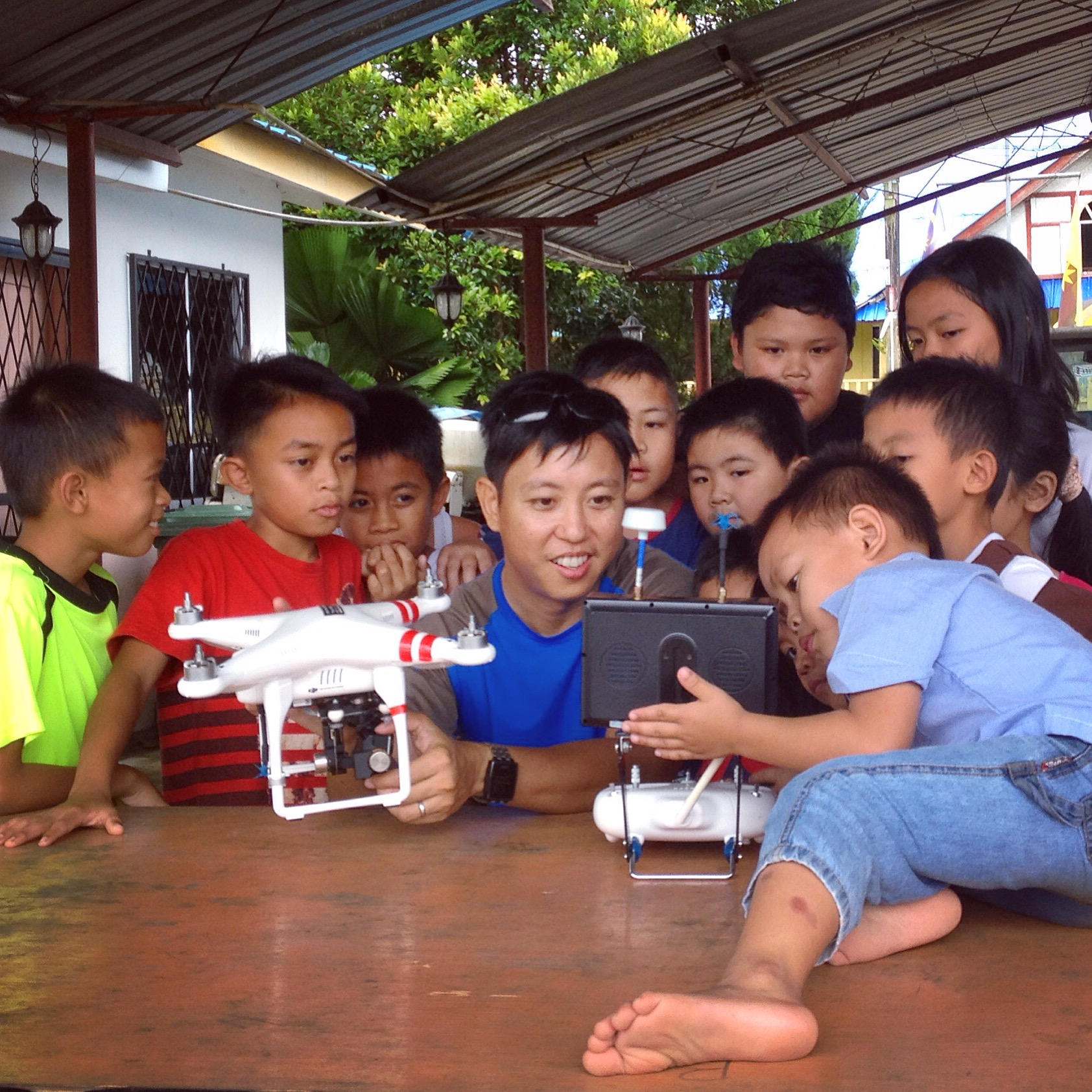 Borneo kids enjoying watching a video clip of themselves from the air.